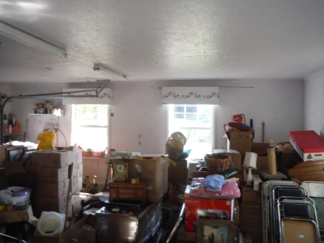 The garage, full of things for the upcoming auction. The owner is very crafty; she did all the painting, etc. in the house. Note the ivy painted on the boxes over the garage windows.