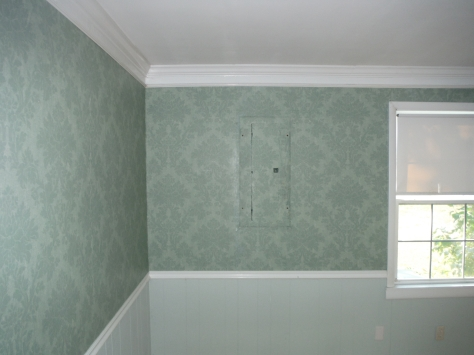 Side (west) wall of the living room.  Note the circuit breaker box cleverly wallpapered to blend in...